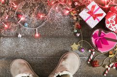Christmas background, light and gift box with child boots Stock Photos