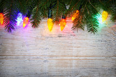 Christmas background with lights on branches. Multicolored Christmas lights on spruce branch with wooden background Stock Photo