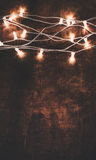 Christmas background with lights garland over wooden background Stock Photos