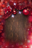 Christmas Background Lights. A Christmas background with presents, red tinsel, ornaments and star lights on a warm rustic wood background Royalty Free Stock Photography