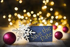 Christmas Background, Lights, Save The Date. Plate With Golden English Text Save The Date. Bright Glowing Lights In The Background. Christmas Ornament Like Red Stock Photos