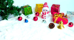 Christmas background. Many color balls and presents and snowman and pine flower and tree on the snow background Stock Photo