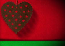 Christmas Background. Metal heart with stars hanging on red and green velvet background with shadows Royalty Free Stock Photography
