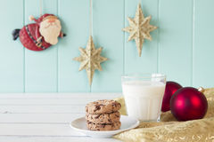 Christmas background. A milk glass and some chocolate chip cookies for Santa. On the background Santa Claus flies between gold stars on a turquoise wooden stock photo