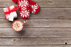 Christmas background with mittens, gift and hot chocolate Stock Photos