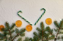 Christmas background. New year decorations with fir branches, candy cones and traditional spices, dried oranges. New Year food royalty free stock images