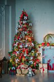Christmas tree with gifts on red background. Christmas background. New Year interior design. Decorated tree near fireplace in great white living room Royalty Free Stock Images