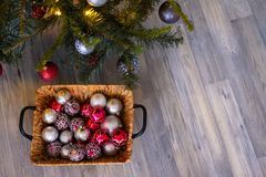 Christmas background. New year`s composition with basket, red and silver balls, a gray background. New Year`s card. Background with copy space stock photos