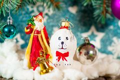 Beautiful dog holding a gift box in mouth by the ribbon for Christmas. Christmas background for notebook diary cover - Christmas tree Santa Claus and dog toy New Stock Photos