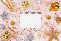 Christmas background with notebook, gift or present box, champagne, confetti and decorations on pink table top view. Flat lay. royalty free stock images