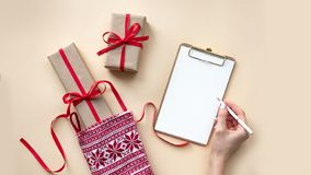 Christmas background with notebook for wish list or to do list, gift boxes. Flat lay royalty free stock photos