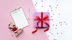 Wooden christmas deer, gift and note on pink and white background. Copy space stock photos