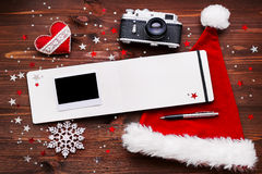 Christmas background with old camera, Ssnta's hat, notepad, photo. Royalty Free Stock Photography