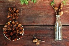Christmas background on old wooden boards with decorative element in the shape of a figure eight, antique bottle and cones of larc Stock Image