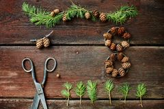 Christmas background on old wooden boards with decorative element in the shape of a figure eight, antique scissors and cones of la Royalty Free Stock Photography