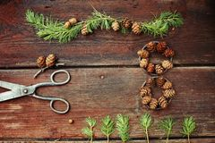 Christmas background on old wooden boards with decorative element in the shape of a figure eight, antique scissors and cones of la Royalty Free Stock Photo