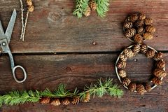 Christmas background on old wooden boards with decorative element in the shape of a figure eight, antique scissors and cones of la Stock Image