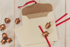Christmas background.Open envelope with golden acorns.White wooden table.Empty space royalty free stock image