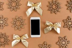 Wood craft snowflakes, bows, mobile phone with copy space on screen on beige background Stock Image