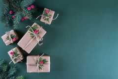 Christmas background. Packing  gifts in vintage beige craft paper and natural decor. Branches of fir and red berry . Royalty Free Stock Photography