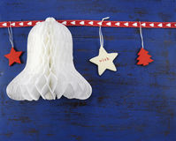 Christmas background with paper bell on dark blue vintage wood. Royalty Free Stock Photo