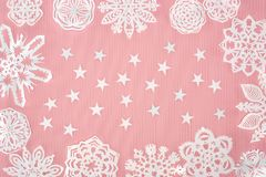 Christmas background with paper snowflakes and stars. On pink Royalty Free Stock Photography