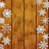 Christmas background with paper snowflakes on wooden planks. Christmas background with white paper snowflakes on brown wooden planks Royalty Free Stock Image