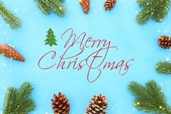 Christmas background with pine cones, fir branches and gifts over wooden blue background. Flat lay, top view stock photos