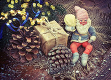 Christmas background with pine cones, ribbons and old gnome Stock Photos