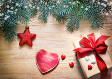 Christmas background. Pine, gift and wooden heart. Royalty Free Stock Image