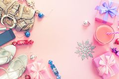 Christmas background pink Flat Lay fashion accessories handbag sandals phone gift box bow balls purple pink. Top view copy space stock image