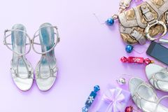 Christmas background pink Flat Lay fashion accessories handbag sandals phone gift box bow balls purple. Top view copy space royalty free stock photography