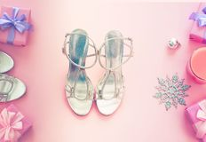 Christmas background pink Flat Lay fashion accessories sandals phone gift box bow balls purple. Top view copy space royalty free stock images