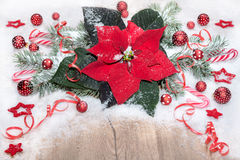 Christmas background with poinsettia, red baubles and snow on wo Royalty Free Stock Photography