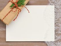 Christmas background of Primed cardboard  lace and a gift in Kra. Christmas background of Primed cardboard for painting , lace and a gift in Kraft paper tied Stock Image