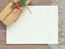 Christmas background of Primed cardboard lace and a gift in Kraf. Christmas background of Primed cardboard for painting , lace and a gift in Kraft paper tied Royalty Free Stock Photography