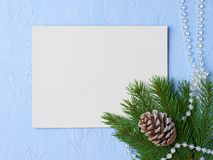 Christmas background Primed cardboard for painting on the backgr. Ound of plaster, fir branches, pine pinecone and beads Royalty Free Stock Image