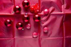Christmas background. Christmas red balls, red candles and red cockade on red satin Royalty Free Stock Photos