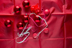 Christmas background. Christmas red balls, red candles and red cockade on red satin Royalty Free Stock Image