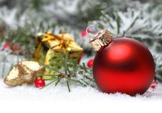 Christmas background with red bauble, berries and fir in snow. Christmas background with a red bauble, berries, golden present and fir in snow Royalty Free Stock Photo