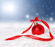 Christmas background with red bauble and merry christmas ribbon. On snow with snowflakes falling from a blue sky Royalty Free Stock Images