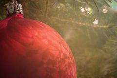 Christmas background with a red bauble and the Christmas tree behind it stock photography