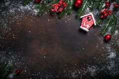 Christmas background with a red bird house. Christmas background with a red bird house, snow, fir branches and decorations on dark stone table. Top view with stock photography