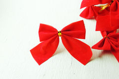 Christmas background, red bows. Shiny red satin ribbon on white background Royalty Free Stock Image