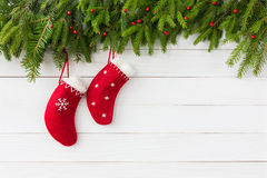 Christmas background. Red Christmas socks on white wooden background with Christmas fir tree. Copy space Stock Images