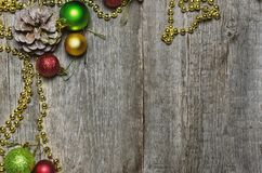 Christmas background with a red, golden, green christmas balls and fir cones.  Royalty Free Stock Photos