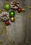 Christmas background with a red, golden, green christmas balls and fir cones.  Royalty Free Stock Image