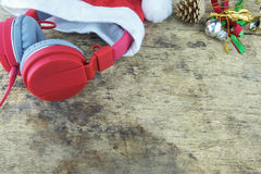 Christmas background. Red headphone in santa Claus hat and christmas decoration staff on wooden background Royalty Free Stock Image