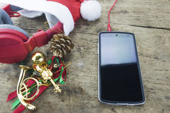 Christmas background. Red headphone in santa Claus hat, smart phone and christmas decoration staff on wooden background Royalty Free Stock Images