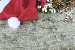 Christmas background. Red headphone in santa Claus hat, smart phone and christmas decoration staff on wooden background Royalty Free Stock Photo